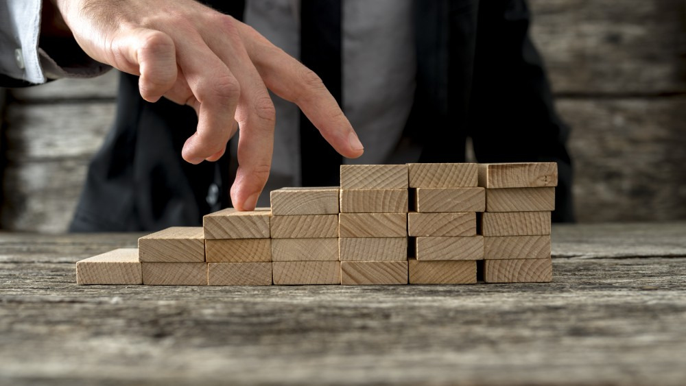 Closeup of businessman walking his fingers up wooden steps. Conceptual of business vision, progress and success.
