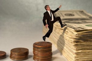 Economic and stock market success concept showing man jumping from coins to cash